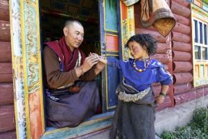 MR 1490-DB 6444 A Tibetan traditional doctor takes the pulse of a nomad girl from Tsatsa in a clinic supported by Shechen humanitarian programs, eastern Tibet. 2005 Un moine médecin tibétain prend le pouls d'une petite fille nomade de la région de Tsatsa, dans une clinique aidée par notre progamme humanitaire. Tibet oriental. Juillet 2005.